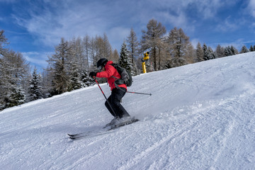Female skier dressed in red jacket enjoys slopes in Italy. Folgaria, Trentino, Italy.