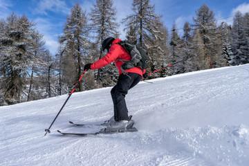 Female skier dressed in red jacket enjoys slopes in Italy. Folgaria, Trentino, Italy.