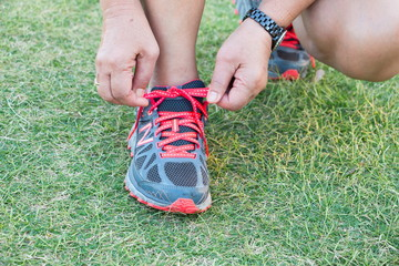 Close up of feet of a runner tying shoe laces in green grass