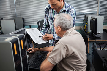 Teacher Showing Clipboard To Student In Computer Class