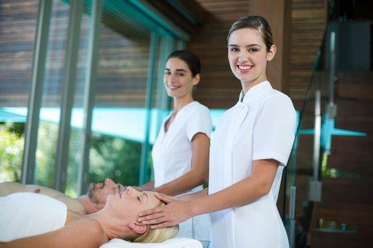 Woman receiving head massage from masseur