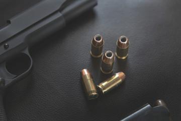 .45 Caliber hollow point bullets near handgun and magazine on le