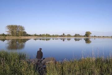 Man on the lake shore platform