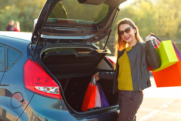 Caucasian woman putting her shopping bags into the car trunk