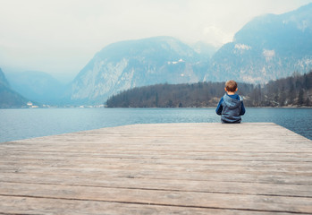Little boy sits on the wooden pier near the blue mountain lake