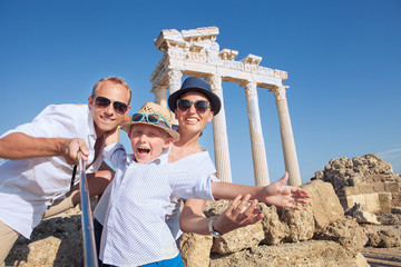 Positive young family take a selfie photo near antique сolonnad