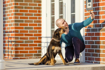 Young man sitting with his dog in front of the door of the house on the porch making selfie copy space