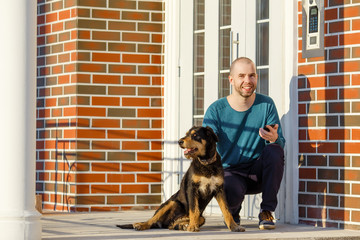 Young man sitting with his dog in front of the door of the house on the porch starting making selfie copy space