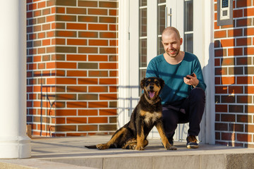 Young man sitting with his dog in front of the door of the house on the porch starting making selfie copy space.