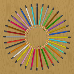 Colored pencils arranged in circle like rays of sun. Color pencils on table.