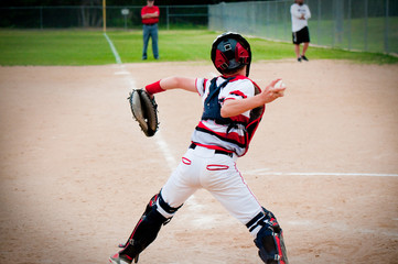 Youth baseball catcher throwing to second base.