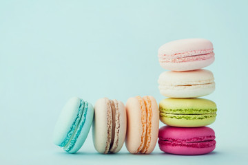 Cake macaron or macaroon on turquoise background, flavor almond cookies, pastel colors, vintage card
