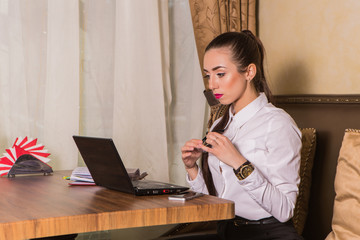 Young woman working with laptop computer in cafe
