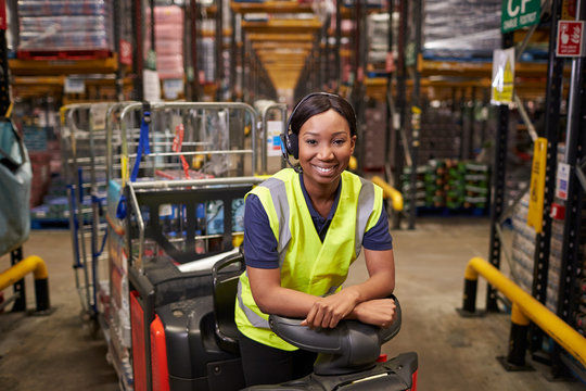 Woman leaning on a tow tractor in a distribution warehouse