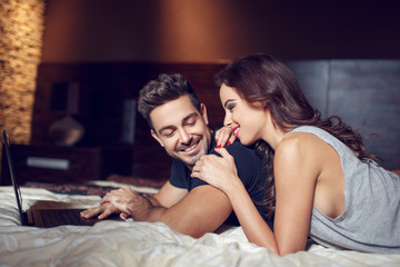 Young couple with laptop lying in bed