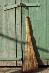 old broom under the old wooden gate