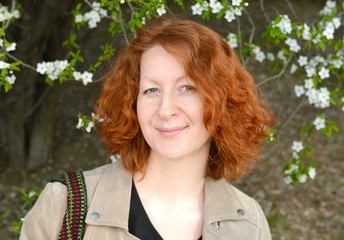 Portrait of a beautiful woman with red curly hair, on a background of a blossoming tree