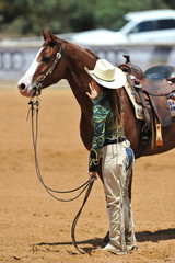 The close-up view of rider in cowboy chaps and hat staying with horse