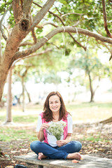 image of a beautiful mature woman in a park scene holding baby's breath flowers. pretty smile.