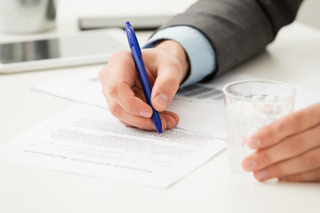 Businessman hand filling in business document