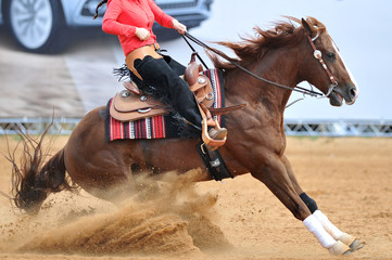 The side view of a rider in cowboy chaps and boots on a horseback running ahead in the dust.