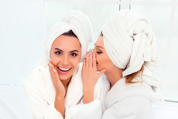 Girl in bathrobe and  towel on her head telling secret to her si