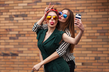 Two young sexy fashion women posing for selfie and laughing with tonque. Lifestyle portrait on street city background