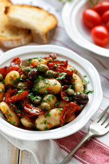 White bean salad with addition of dry tomatoes,  olives, capers and fresh parsley