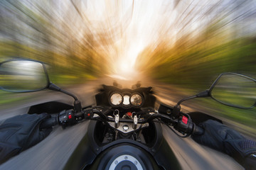 Hands on the steering wheel while driving a motorcycle at speed.