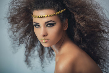 Mulatto girl with curly hair. Portrait in the studio.