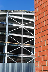Steel building construction and the wall of red brick.
