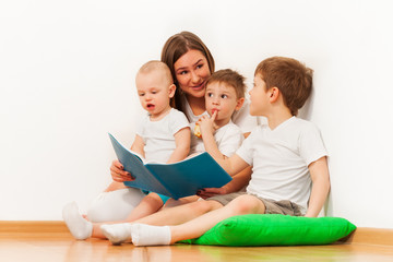 Young mother reading book to her age-diverse kids