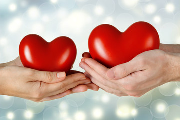 Fototapete - Female and male hands holding red hearts on blurred background. Family, love and health care concept