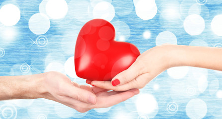 Fototapete - Female and male hands holding red heart on blurred background. Family, love and health care concept
