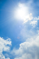 View of blue sky with sun and sunrays between the clouds