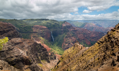 Beautiful Waipoo falls in Waimea Canyon Kauai Hawaii drops 800 feet to the valley floor. This huge colorful canyon on Hawaii's garden Isle is the result of thousands of years of water erosion .
