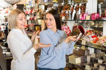 Happy women buying chocolate bars .