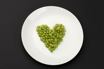 green soya beans arranged in heart shape.
