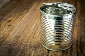 Tin can for food on wooden background with place for your text