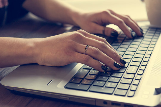Side view of woman's hands writing on laptop.