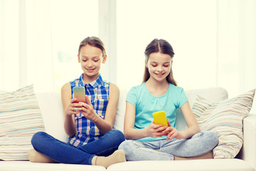 happy girls with smartphones sitting on sofa