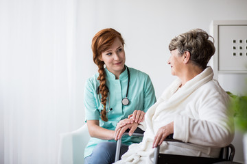 Doctor supporting ill senior woman
