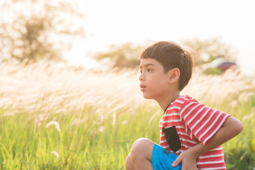 Little boy sitting with golden grasses field sunset time