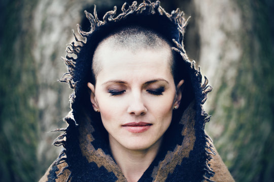 Closeup portrait of beautiful Caucasian white young bald girl woman with shaved hair head with closed eyes, her head covered with scarf shawl, spiritual mood state of mind