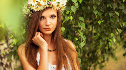 young beautiful woman outdoor in a birchwood wearing wreth of daisy
