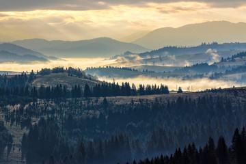 cold fog on hot sunrise in mountains