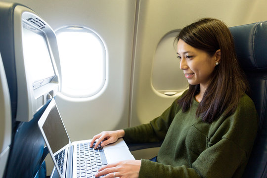 Woman working with laptop computer at airplane