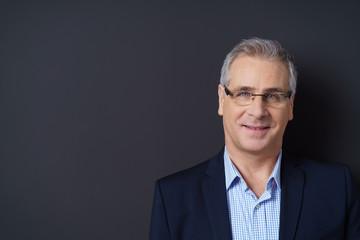 mann mit brille und anzug vor grauer wand