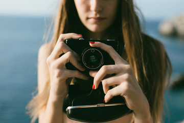 Portrait of blonde girl on the beach with a camera