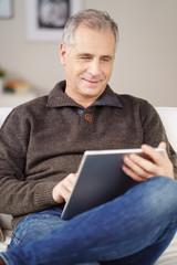 mann sitzt auf dem sofa und liest am tablet